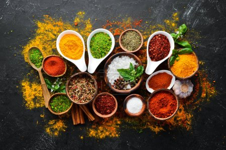 Photo for Colorful herbs and spices for cooking. Indian spices. On a black stone background. Top view. - Royalty Free Image