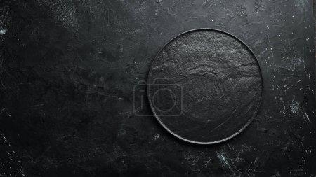 Photo pour Assiette en pierre noire sur fond noir. Vue de dessus. Espace libre pour votre texte . - image libre de droit