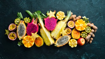 Photo for Tropical fruits - passion fruit, pineapple, dragon fruit, kiwi and cactus on a black background. Top view. Free space for text. - Royalty Free Image