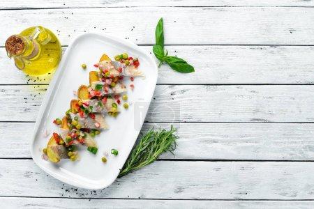 Photo pour Hareng avec pommes de terre cuites au four dans une assiette. Plats de restaurant. Vue du haut. Espace libre pour votre texte. - image libre de droit