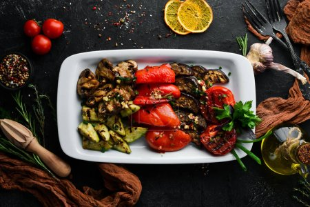 Grilled vegetables on a plate. Tomatoes, eggplants, mushrooms, zucchini. Dishes, food. Top view. Free space for your text.