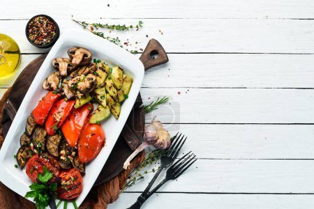 Photo for Grilled vegetables on a plate. Tomatoes, eggplants, mushrooms, zucchini. Dishes, food. Top view. Free space for your text. - Royalty Free Image