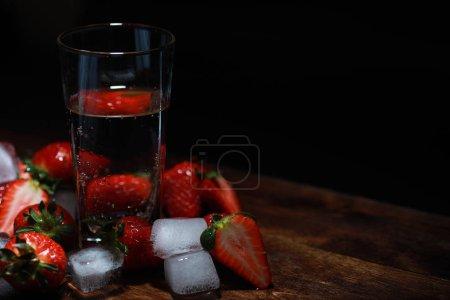 Photo pour Fraises fraîches mûres sur une table en bois et glaçons à l'eau - image libre de droit