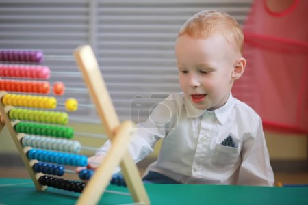 Photo for A small child is playing with toy accessories - Royalty Free Image