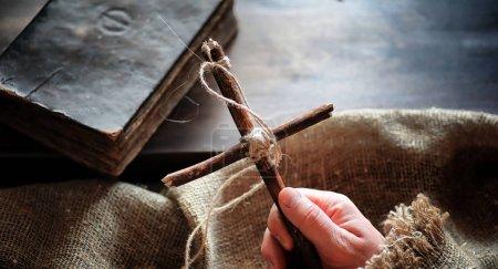 Photo pour Vieux livre religieux sur une table en bois. Une croix religieuse attachée avec une corde et une toile de jute à côté de la Bible. Culte, péchés et prière . - image libre de droit