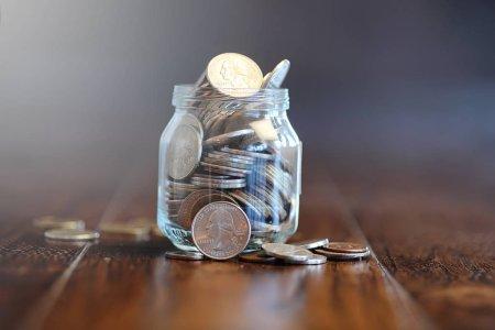 Photo pour Pièces de monnaie dans un bocal en verre sur un plancher en bois. Économies de poche de pièces de monnaie à la Banque. Tirelire en pot de verre avec pièces. - image libre de droit