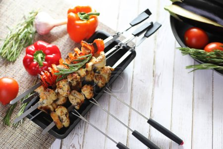 Kebab cooked on metal skewers with vegetables