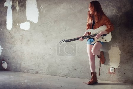 Young red-haired girl with an electric guitar. Rock musician gir