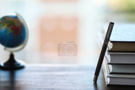 Photo for A stack of textbooks on the windowsill and writing utensils - Royalty Free Image