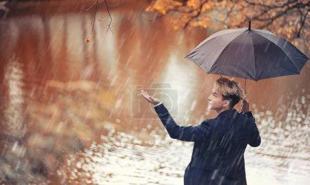 Photo pour Parc d'automne par temps pluvieux et un jeune homme avec un parapluie - image libre de droit