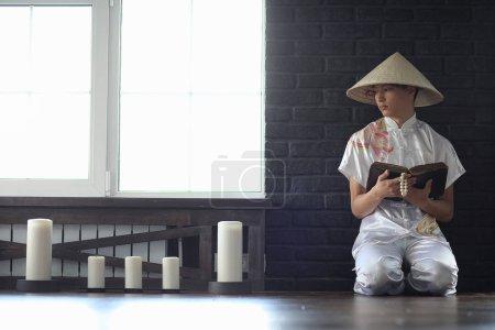 Photo pour Asiatique garçon dans kimono lecture un vieux livre assis par la fenêtre - image libre de droit