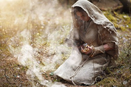Photo for A man in a cassock spends a ritual in a dark forest with a crystal ball and book - Royalty Free Image