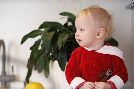 Photo pour Petit enfant blond dans la cuisine se trouve sur une table - image libre de droit