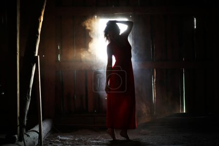 Photo for Silhouette of a beautiful girl in a red dress on the background of a window in an old hous - Royalty Free Image