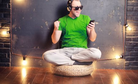 Photo for Young man listening to music with headphones sitting on the floo - Royalty Free Image