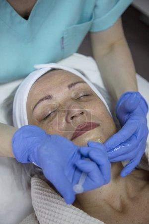Photo pour Portrait de femme d'âge moyen ayant un traitement du visage à la clinique de beauté - image libre de droit