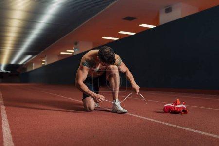 Photo pour Homme très en forme sur une piste intérieure se préparant à courir en caressant ses chaussures et en attachant ses lacets - image libre de droit