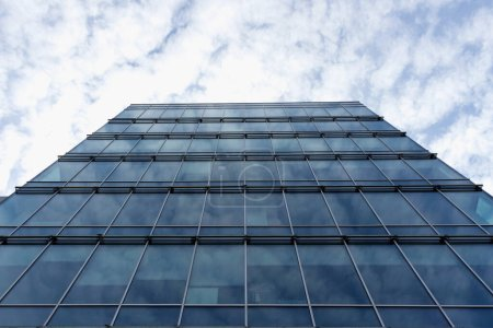 Photo pour Abstract a fragment of modern architecture, walls of glass  on a background of blue cloudy sky. - image libre de droit
