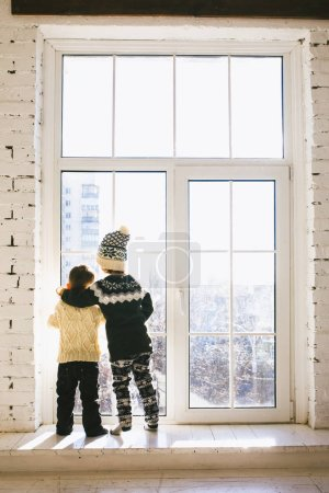 Theme Christmas morning. Two baby Caucasian boy and girl brother and sister standing with backs on window front of large box in embrace in winter knitted woolen clothes and hat of house in sunny day.