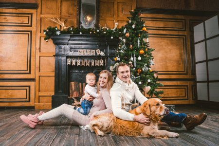 Theme Christmas and New Year family circle. Young Caucasian family with 1 year old child dog breed Labrador Golden Retriever sitting on wooden floor home in living room near fireplace Christmas tree.