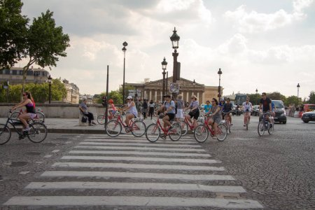 Photo for Paris, France - July 06, 2018: A group of cyclists and cars crosses the Pont de la Concorde and the view of the National Assembly in Paris - Royalty Free Image