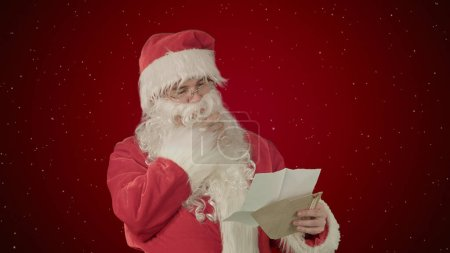 Photo for Santa Claus reading letters from children on red background with snow. Professional shot on BMCC RAW with high dynamic range. You can use it e.g in your commercial video, christmas holiday video - Royalty Free Image
