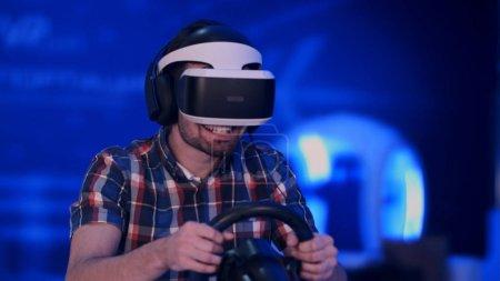 Photo pour Jeune homme heureux dans un casque de réalité virtuelle jouant au jeu vidéo avec volant de course. Tir professionnel en résolution 4K. 079. Vous pouvez l'utiliser par exemple dans votre vidéo commerciale, d'affaires, de divertissement - image libre de droit