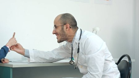 Smiling doctor giving little patient a lollipop after the exam
