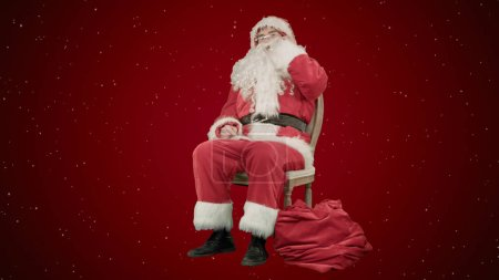 Photo for Santa claus calling by mobile cell phone on red background with snow. Professional shot on BMCC RAW with high dynamic range. You can use it e.g in your commercial video, christmas holiday video, santa - Royalty Free Image