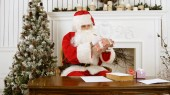 Santa Claus sitting at the table in his Christmas workshop signing presents for children