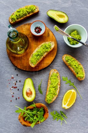 Photo for Flat lay of avocado toasts and ingredients. Good fats raw healthy eating concept. - Royalty Free Image