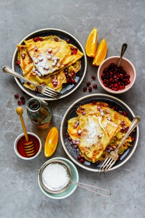 Photo for Flat-lay of sweet crepes topped with pomegranate. Thin pancakes, fruits, honey and maple syrup - Royalty Free Image