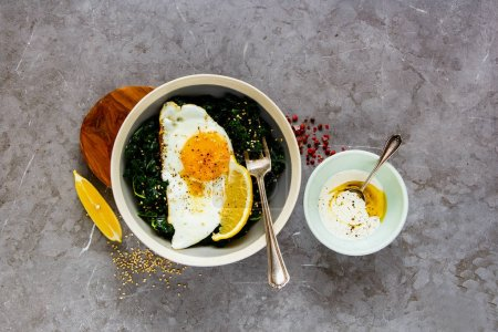 Photo for Fresh vegetarian lunch bowl. Flat-lay of breakfast with fried egg, kale and sesame seed over grey background, top view. Healthy diet food concept - Image - Royalty Free Image