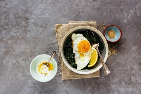 Photo for Vegetarian lunch bowl. Flat-lay of breakfast with fried egg, kale and sesame seed over grey background, top view. Healthy diet food concept - Image - Royalty Free Image