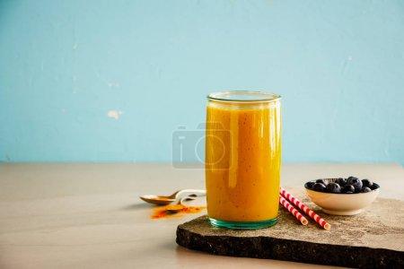 Photo pour Mangue banane Curcuma smoothie pot sur fond bleu - image libre de droit