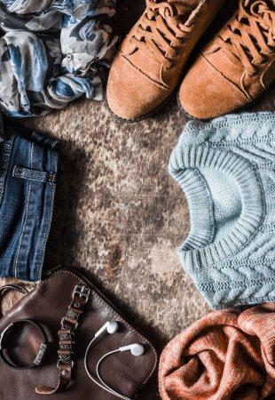 Photo pour Ensemble d'automne de vêtements pour femmes - chaussures en daim, jeans, pull tricoté, écharpe, sac à bandoulière, accessoires sur un fond en bois, vue sur le dessus. Style urbain, plan plat - image libre de droit