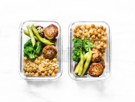Photo for Healthy lunch box - spicy couscous with chickpeas, broccoli, green beans and turkey meatballs on dark background, top view. Copy space - Royalty Free Image