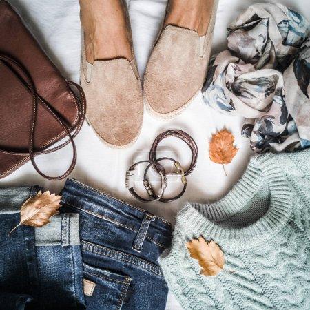 Photo pour Ensemble de vêtements d'automne pour femmes - jeans, baskets en daim, pull, écharpe et sac en cuir. Les pieds des femmes en baskets en daim entourées de vêtements pour des promenades automnales sur un fond clair, vue sur le dessus. Pose plate - image libre de droit