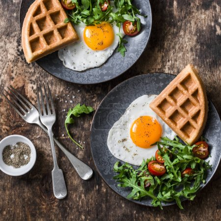 Photo for Whole wheat savory waffles, fried eggs and arugula, cherry tomato salad - healthy breakfast on wooden background, top view - Royalty Free Image