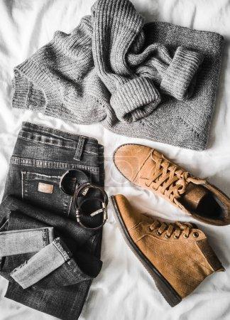 Photo pour Ensemble de vêtements d'automne et d'hiver pour femmes sur un fond clair - jeans, pull surdimensionné gris, bottes en daim marron et écharpe. Vêtements à la mode pour les promenades, pose plate - image libre de droit