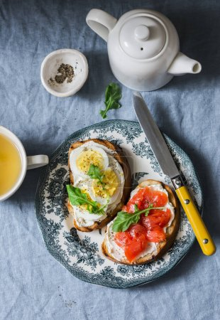 Photo for Delicious healthy breakfast or snack - sandwiches with cream cheese, boiled egg and smoked salmon and green tea on a blue background, top view - Royalty Free Image