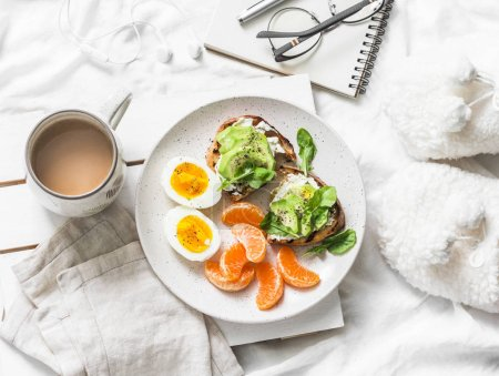 Photo for Womens cozy breakfast in bed still life - coffee, avocado sandwiches, boiled egg and tangerine on a light background, top view. Morning inspiration plan - Royalty Free Image