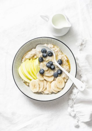 Photo for Steel-cut oats breakfast porridge with apple, banana, blueberry and honey on a light background, top view. Vegetarian healthy food - Royalty Free Image