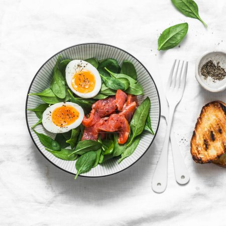 Photo for Delicious brunch - spinach, smoked salmon, soft boiled egg on a light background, top view. Healthy eating diet concept - Royalty Free Image