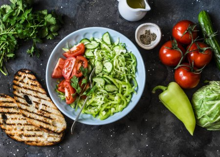Photo for Fresh seasonal cabbage, cucumbers, peppers, tomatoes, cilantro salad and grilled bread on a dark background, top view. Healthy vegetarian diet food - Royalty Free Image