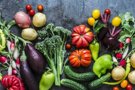 Photo for Fresh seasonal vegetables food background. Aubergines, tomatoes, radishes, peppers, broccoli, potatoes, beets on a dark background, top view. Flat lay - Royalty Free Image
