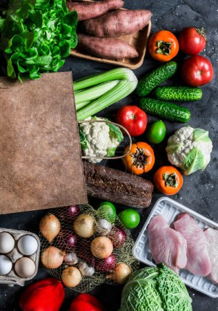 Photo for Grocery concept. Paper bag with fresh organic vegetables, fruits, turkey meat on a dark background, top view. Healthy diet food concept - Royalty Free Image