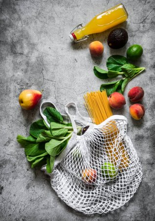 Photo for Healthy food planning concept. Eco bag, fruits, vegetables, greens, pasta on a gray background, top view with copy space - Royalty Free Image