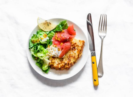 Photo for Spanish potato tortilla with greek yogurt, smoked salmon and green salad on a light background, top view - Royalty Free Image