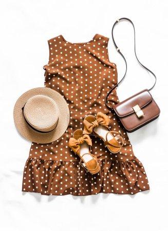 Photo pour Tenue femme été look - robe sans manches à pois marron, sandales en daim, sac bandoulière en cuir, lunettes de soleil et chapeau sur un fond clair, vue sur le dessus - image libre de droit